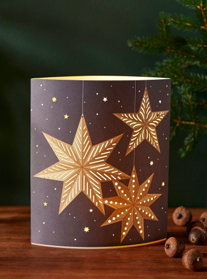 A paper lantern with star patterns on a wooden shelf