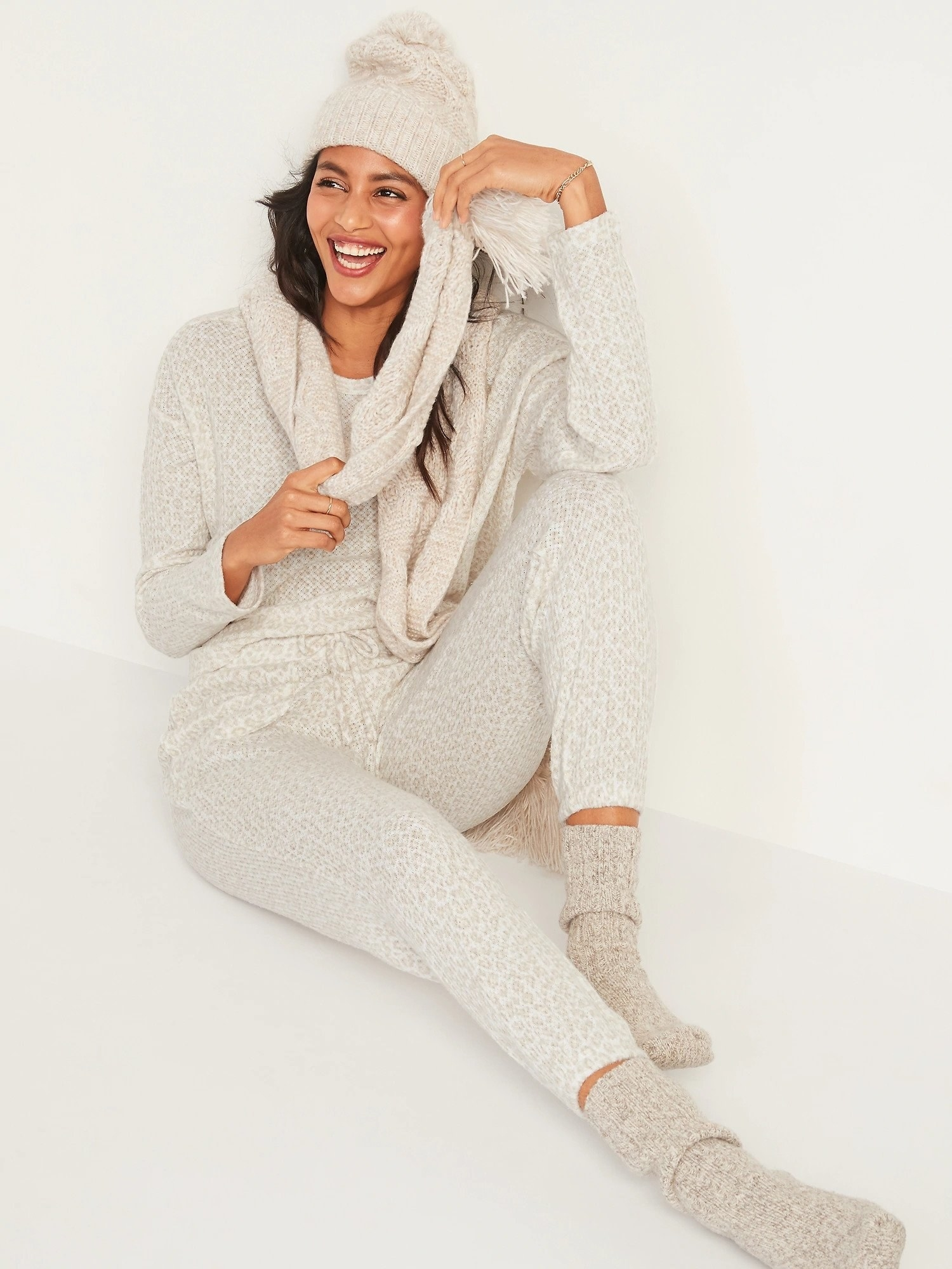 A woman wearing white leopard print jogger style lounge pants and a matching top scarf socks and hat