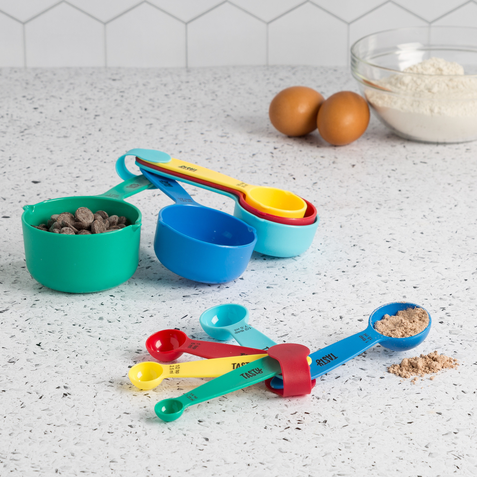 The measuring cups spread out and holding ingredients to show the sizes of each