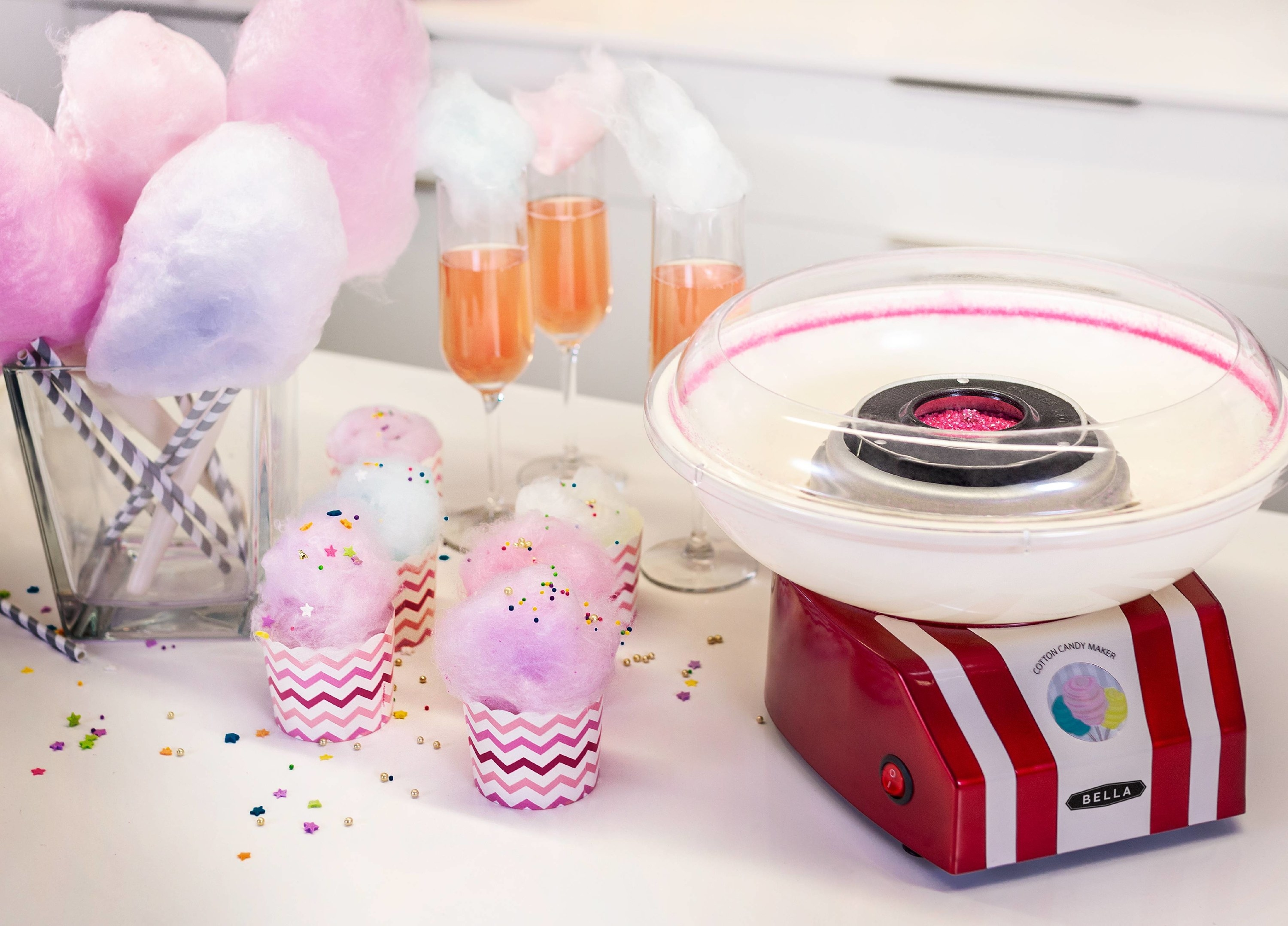 cotton candy maker on a counter with blue and pink cotton candy in the background