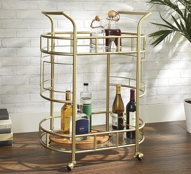 gold better homes & gardens bar cart with bottles on the bottom and top