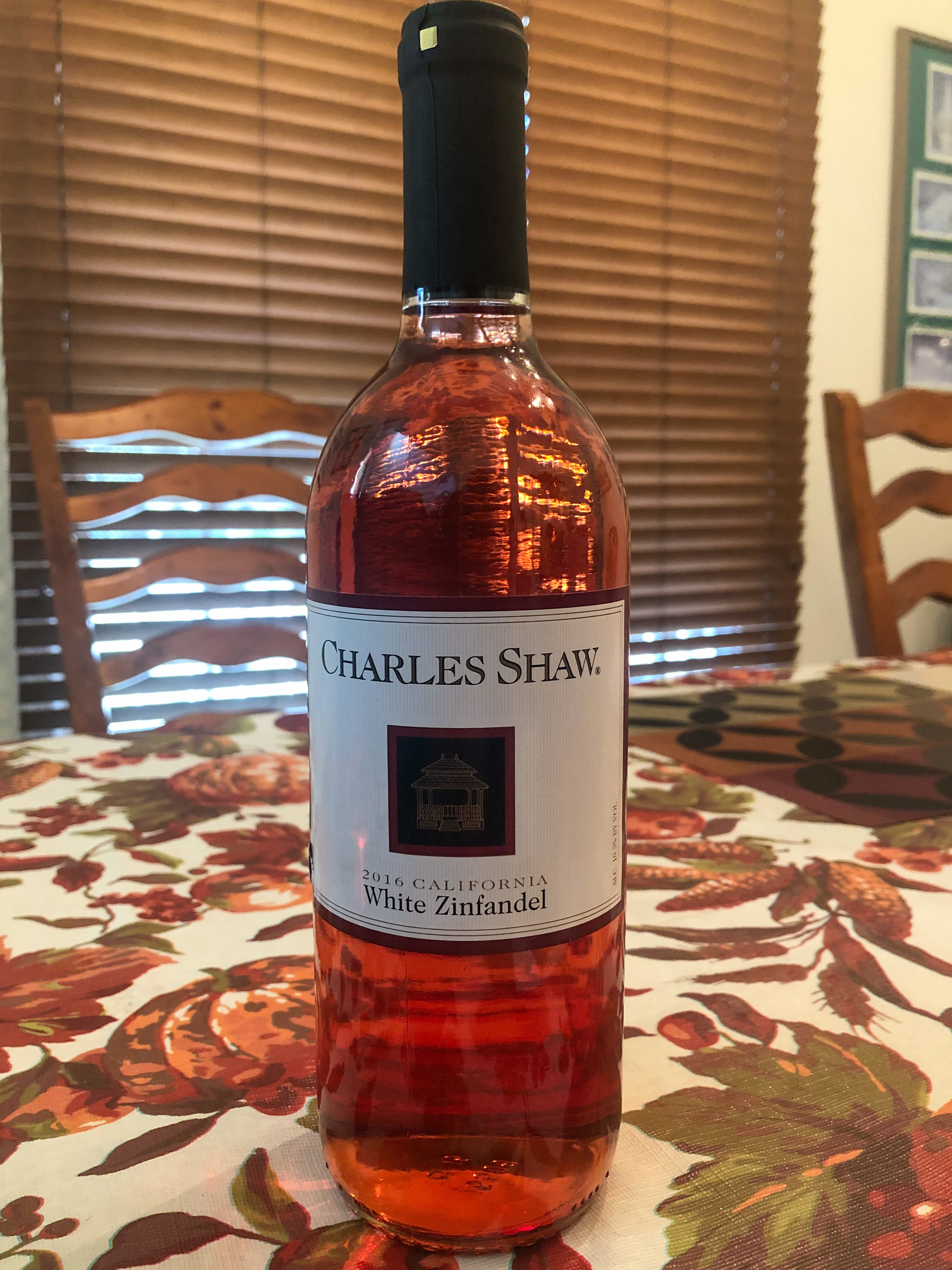 A bottle of Charles Shaw white zinfandel on a table