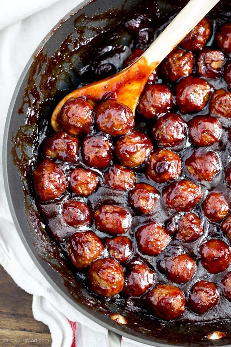 A skillet of cranberry mini meatballs in sauce.