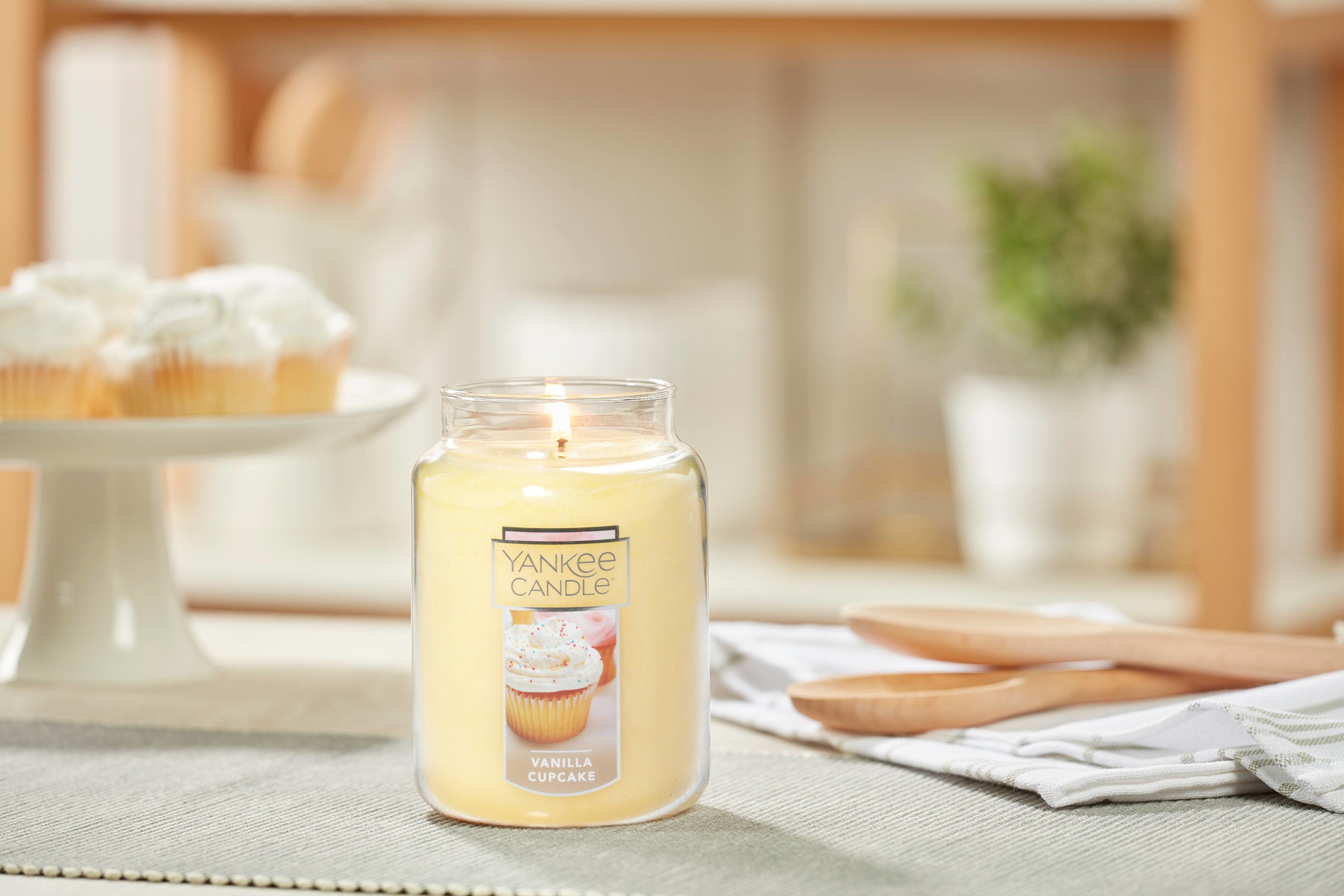 The Yankee Candle on a kitchen table beside vanilla cupcakes