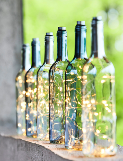 Six glass bottles filled with twinkling lights on a window sill