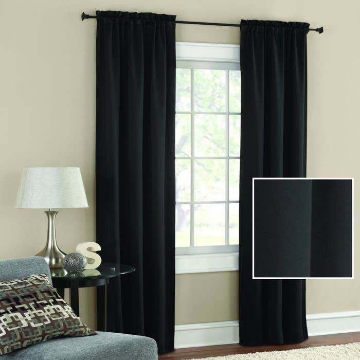 The blackout curtains in black hung over a window to show their length