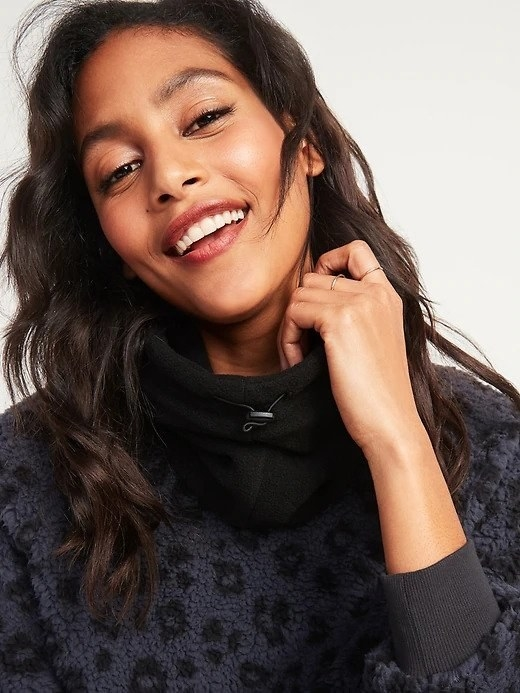 A woman wear a black fleece snood over the collar of a black leopard print sweater