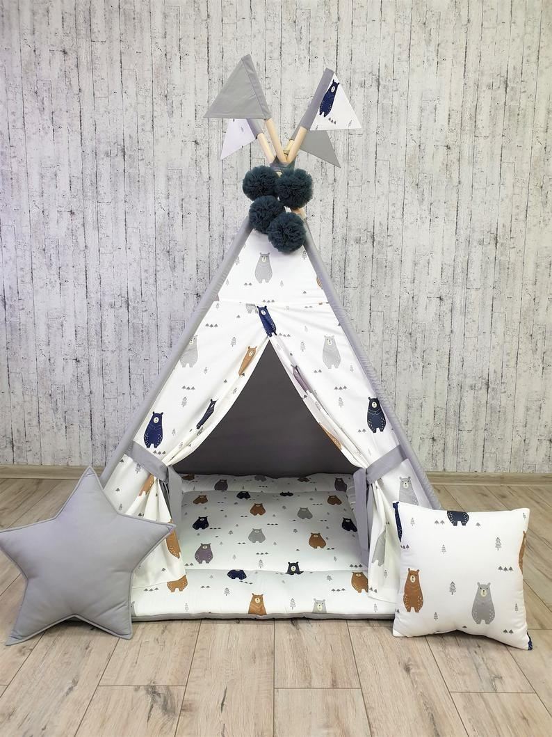 A soft white and gray tent with bear pattern and pillows and floor mat
