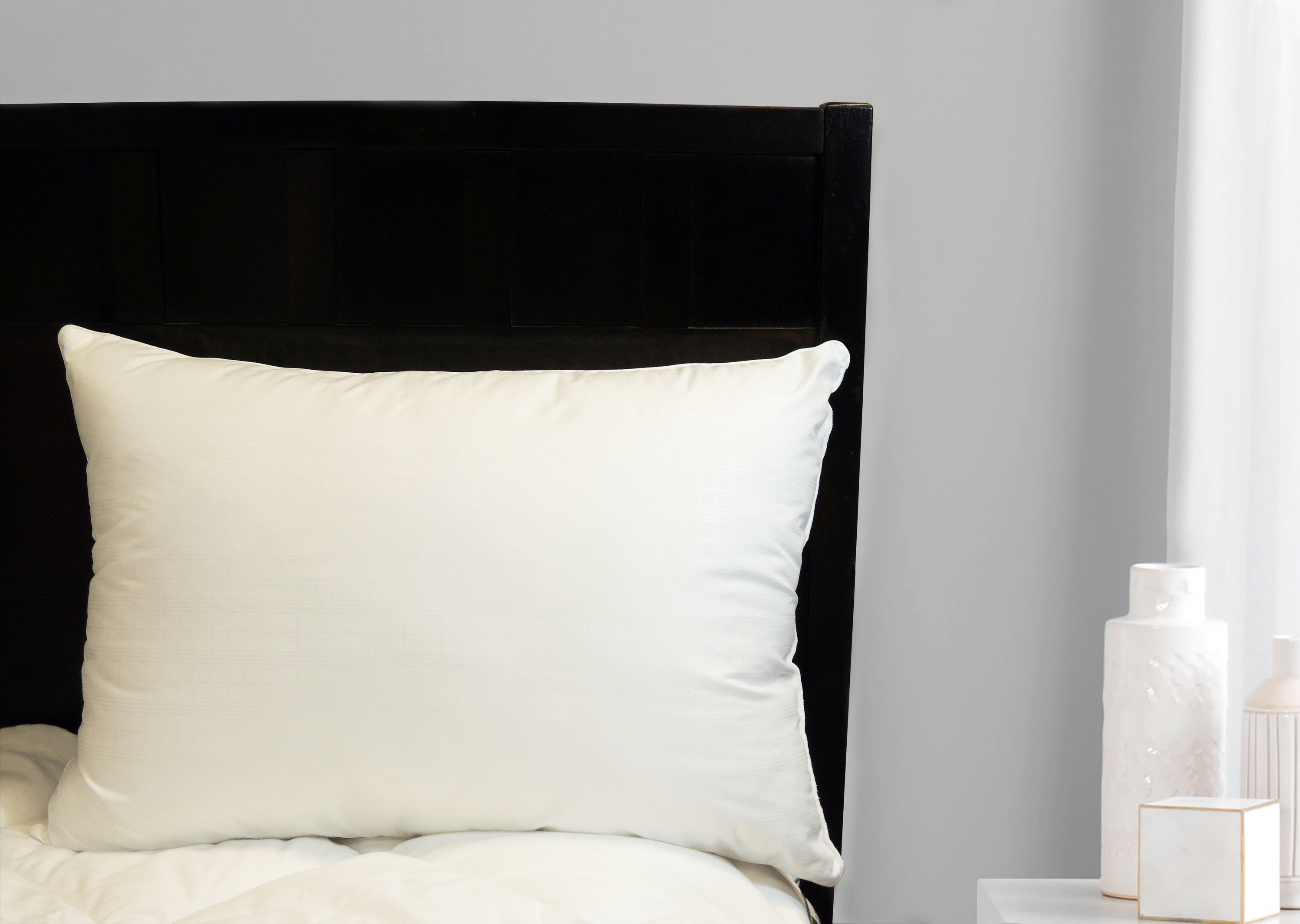 The pillow on a bed with a dark headboard