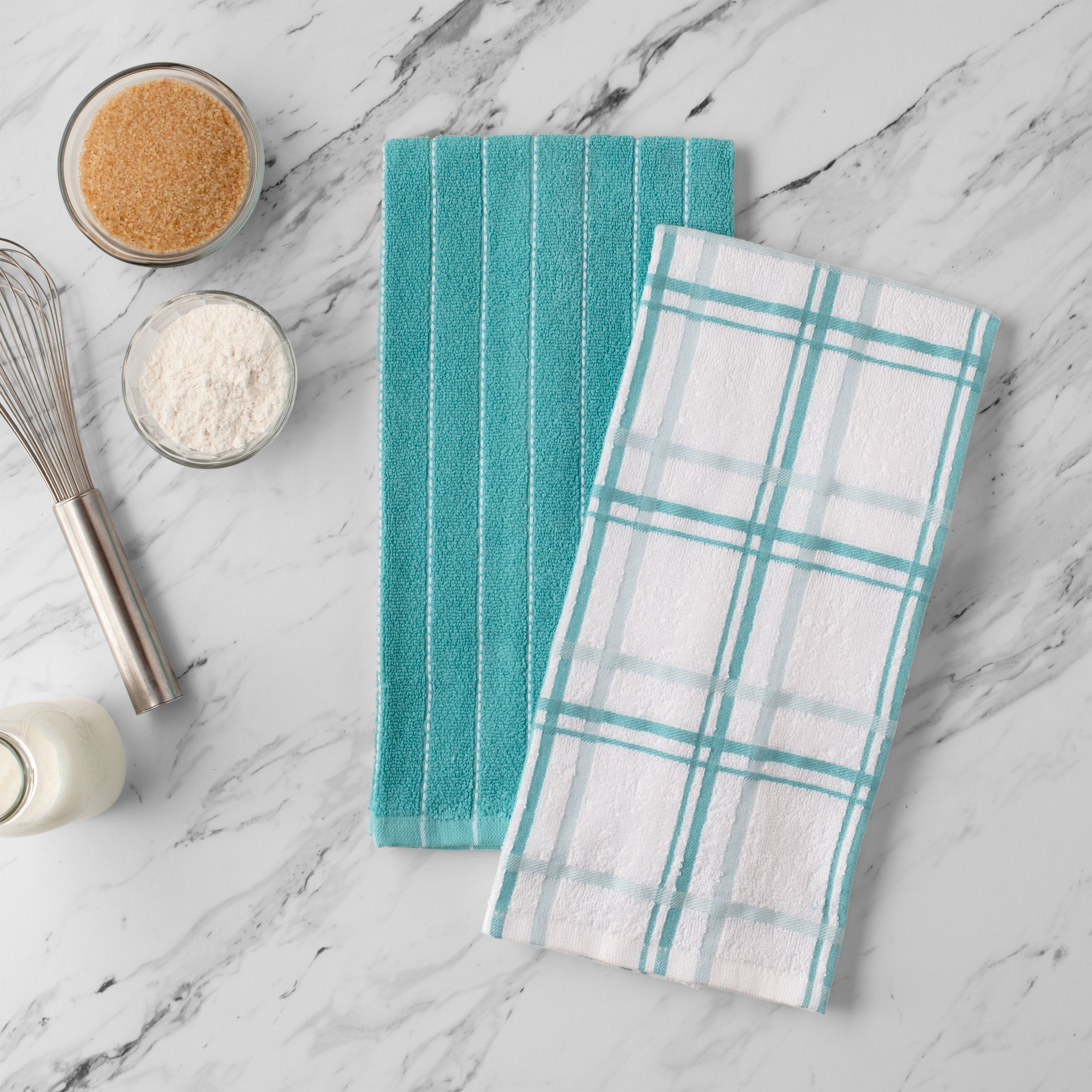 The dish towel set on a marble counter in the color aqua blue