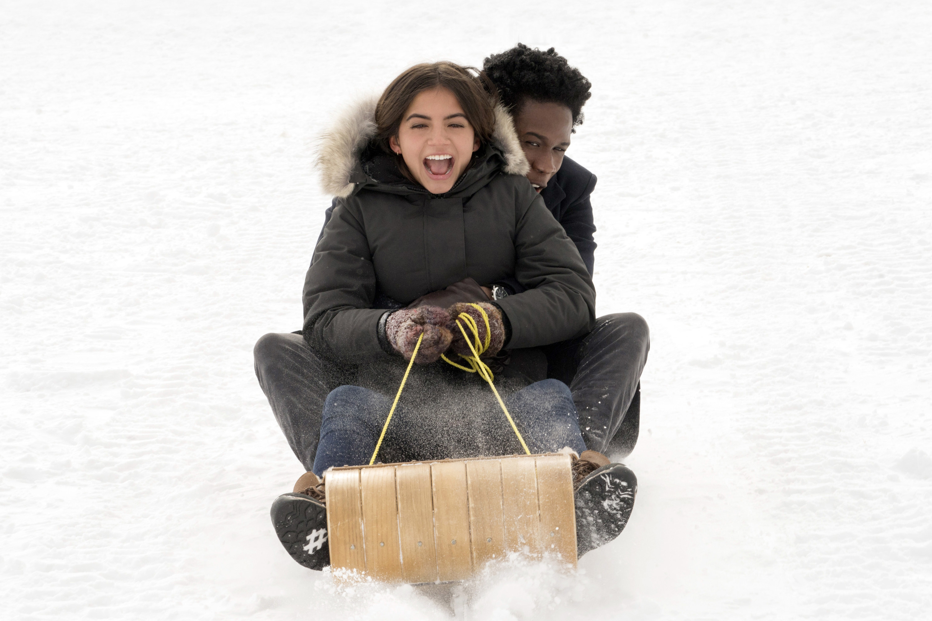 Two of the teenagers in Let It Snow sledding down the hill.