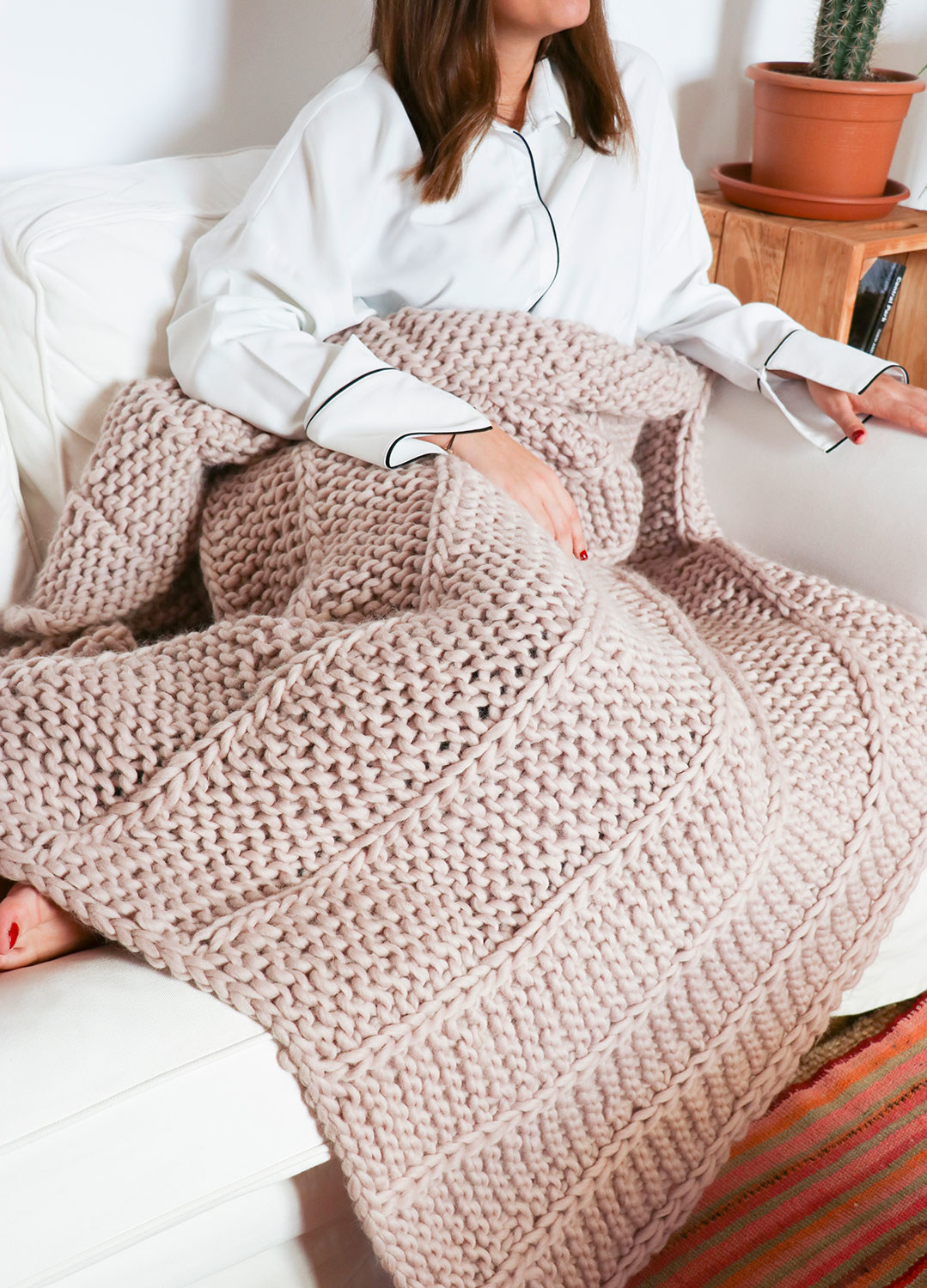 Modl with a large chunky knit blanket in light pink over their lap
