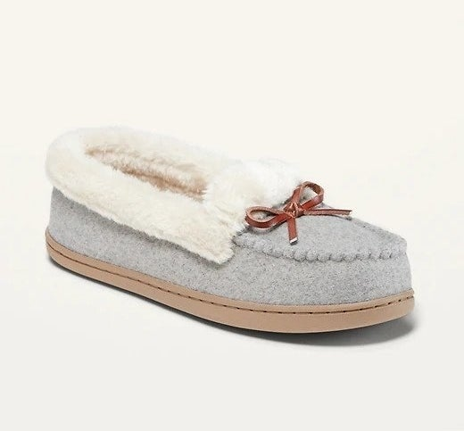 A pair of grey and brown moccasin slippers with white faux-fur inside