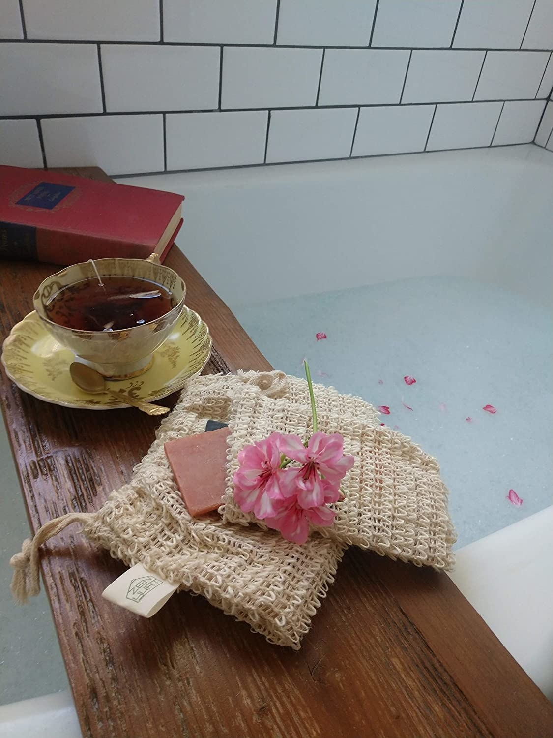 a thick wooden bath tray laid across a tub with a cup of tea, soap, and a book resting on the tray