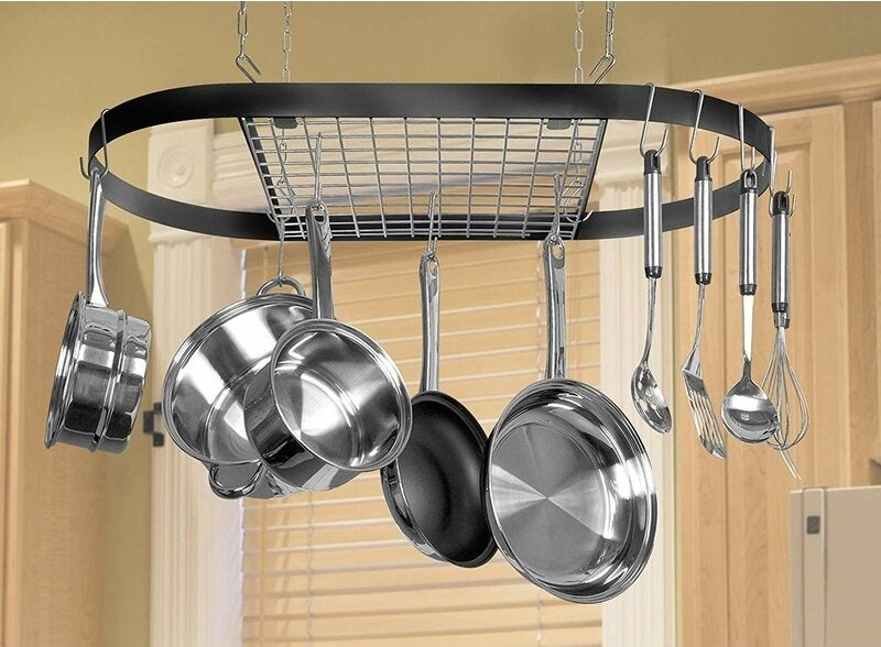 Black wrought iron pot rack with silver pots and pans hanging