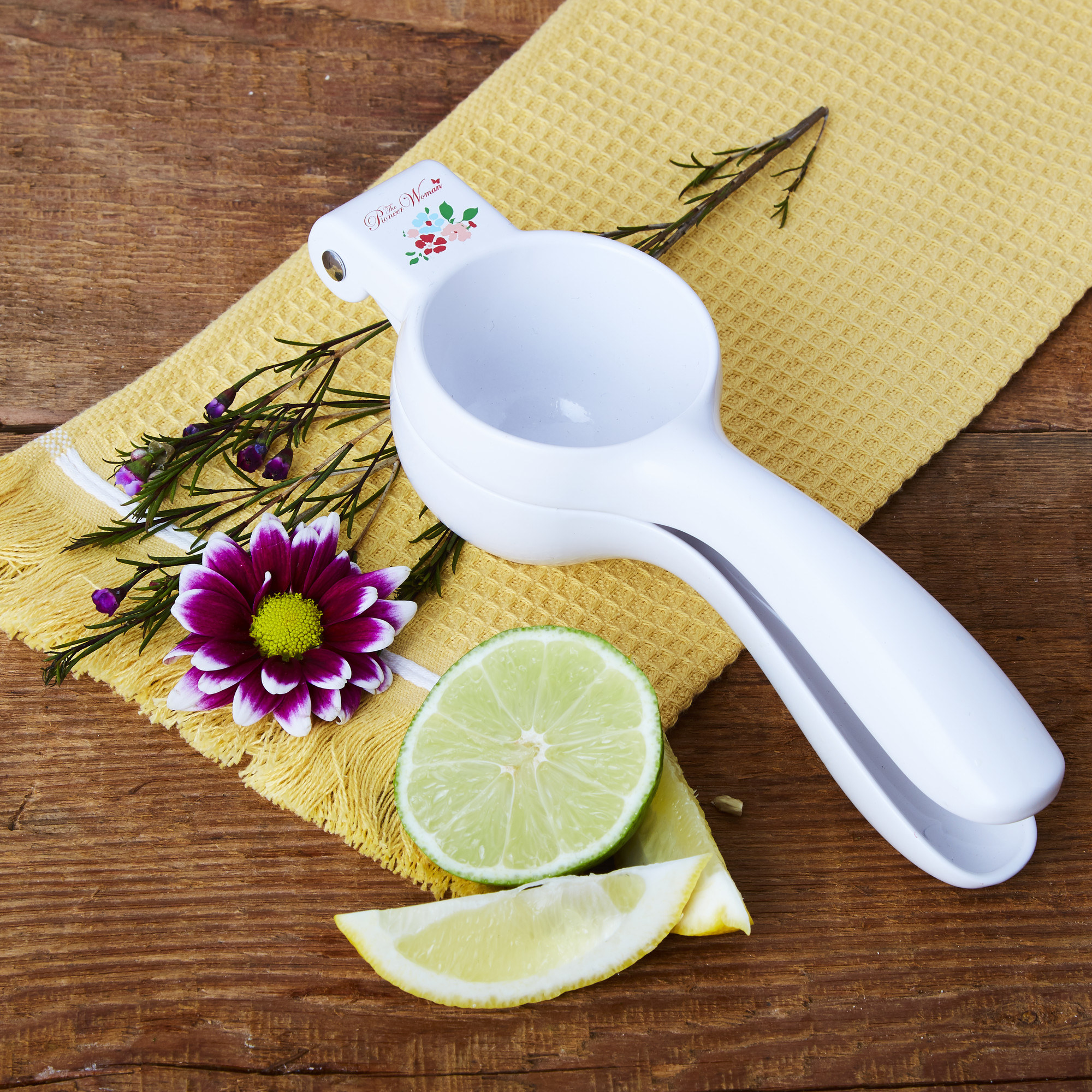 The citrus press beside a lemon and lime on a yellow dish towel