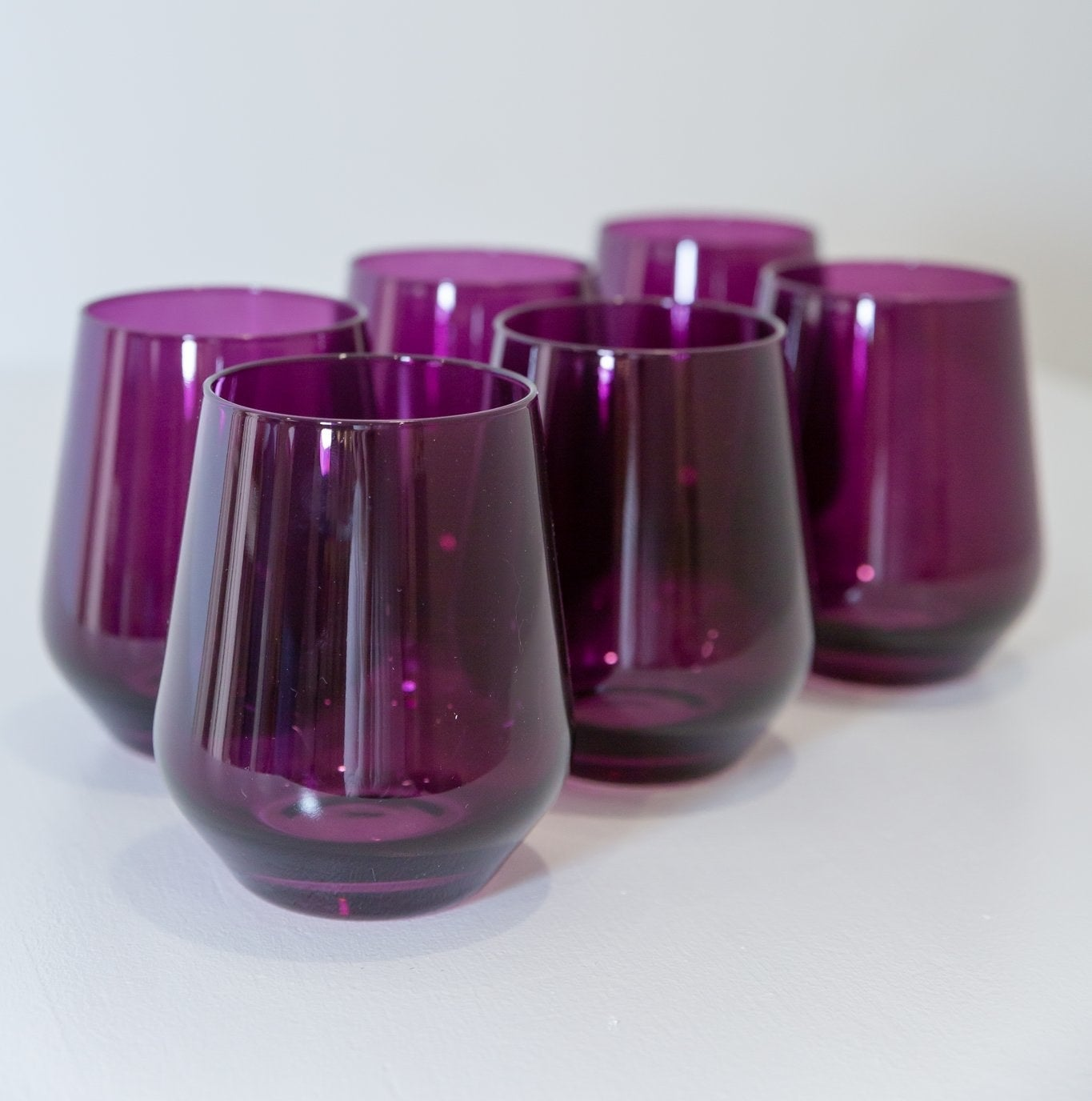 A set of six stemless wine glasses in a dark purple color