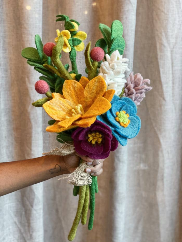 hand holding a bouquet of all different types and colors of flowers made out of felt