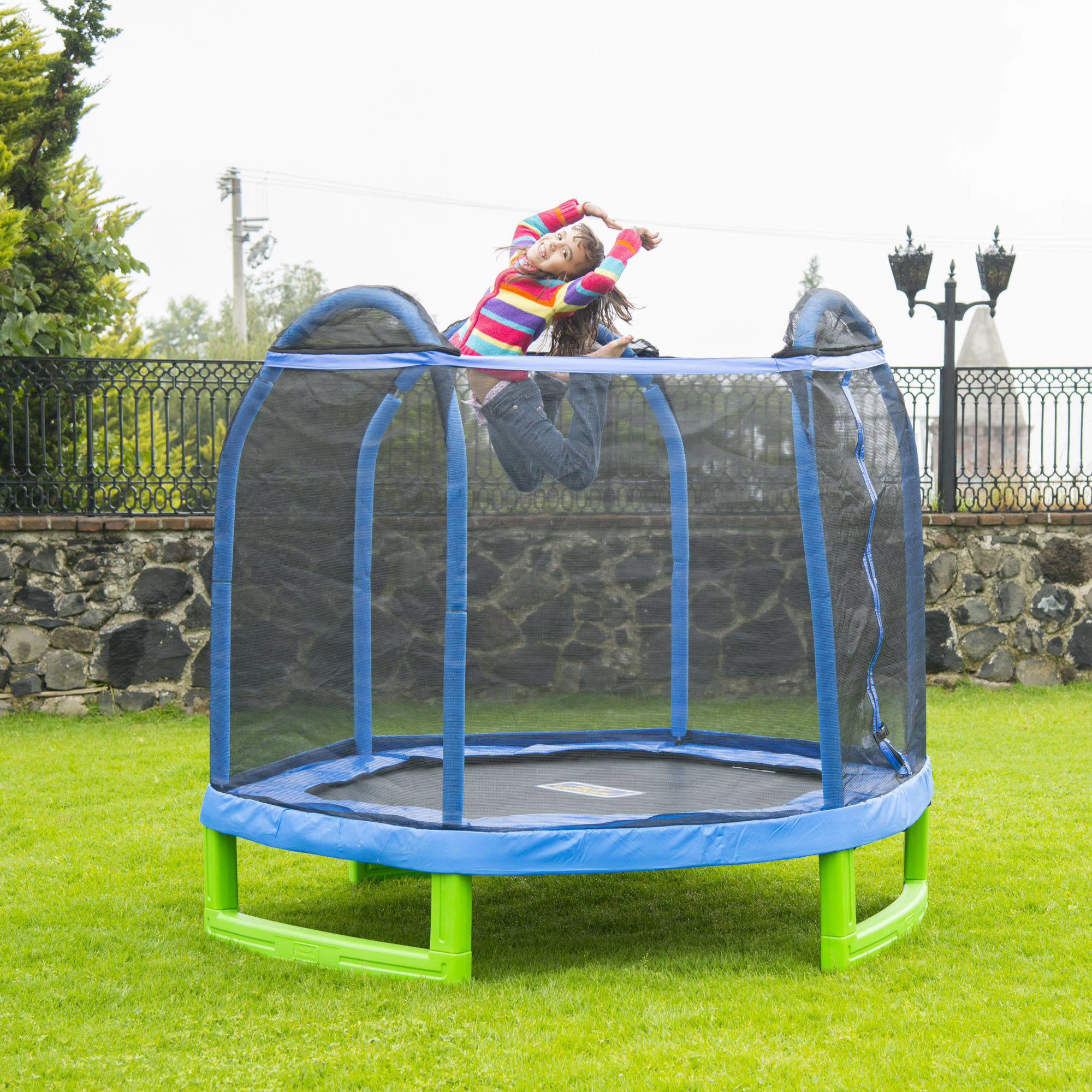 child jumping on an enclosed trampoline while smiling at the camera