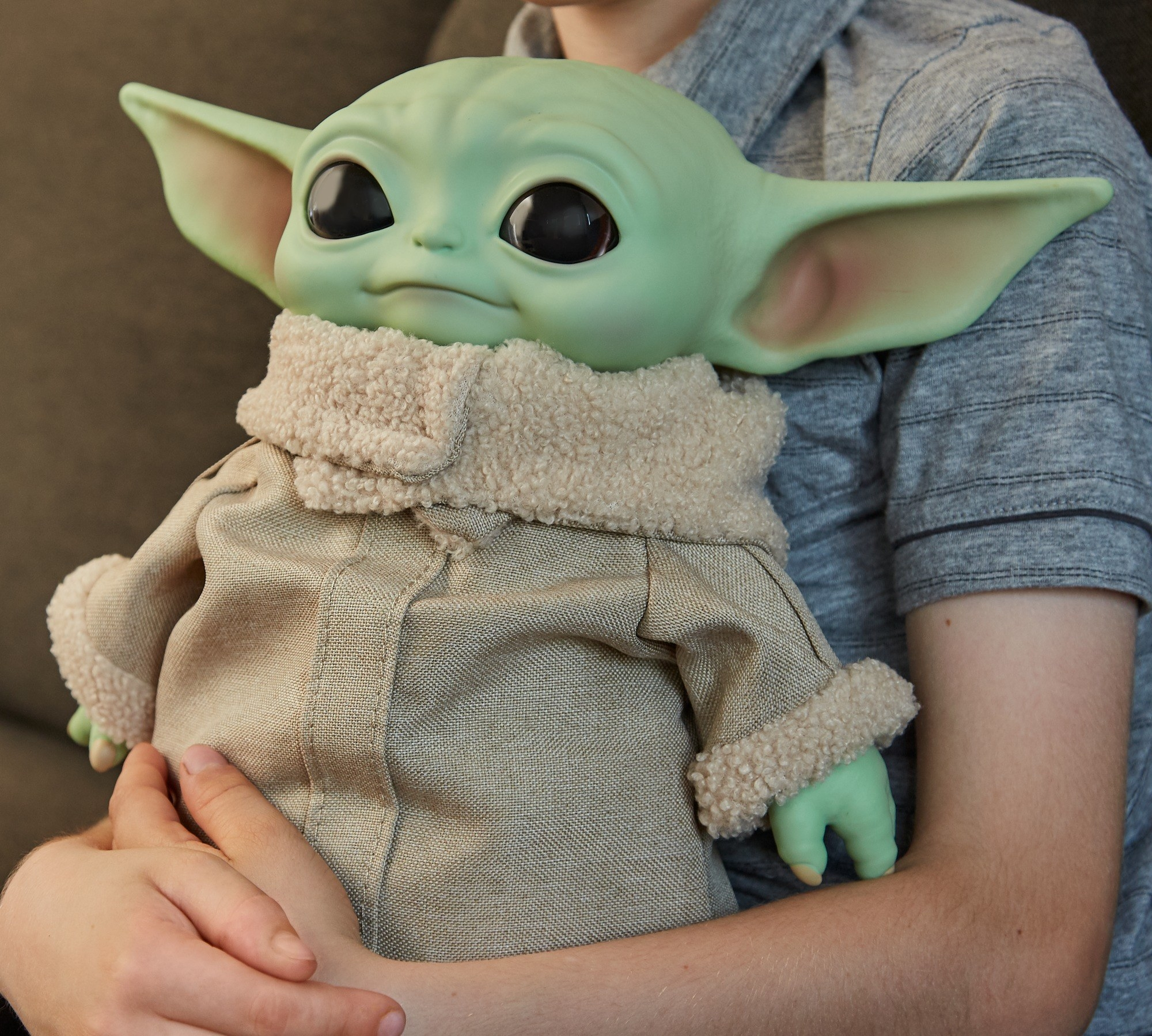 child hugging a baby yoda plush toy