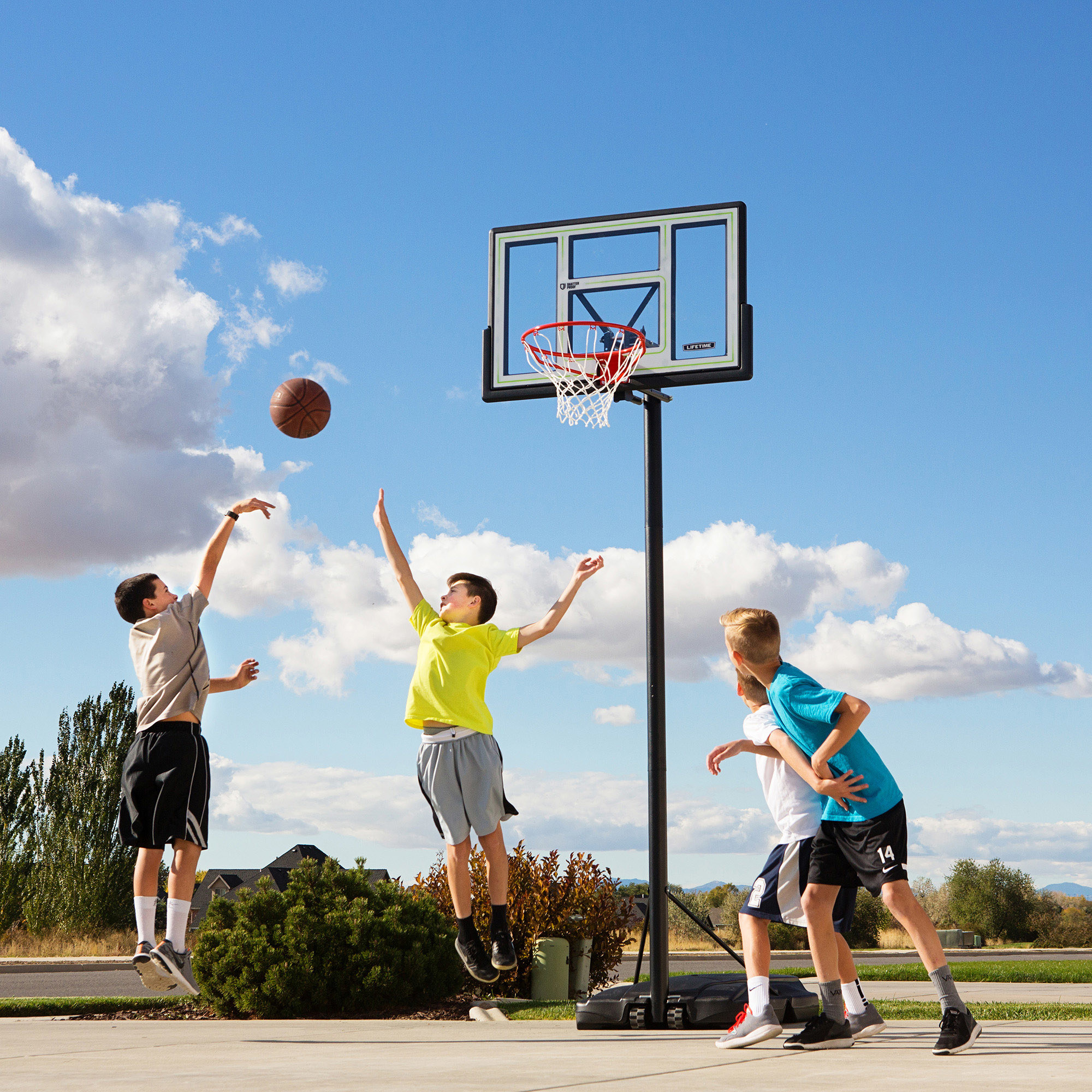 group of kids playing basketball with an adjustable basketball hoop in a front yard