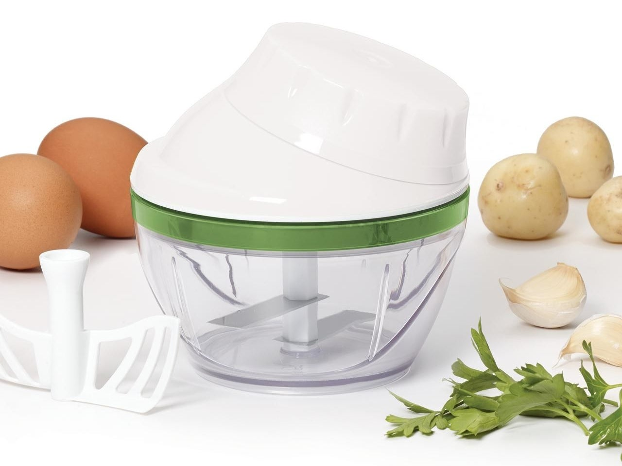 The vegetable spin chopper next to a beater attachment and surrounded by vegetables and garlic