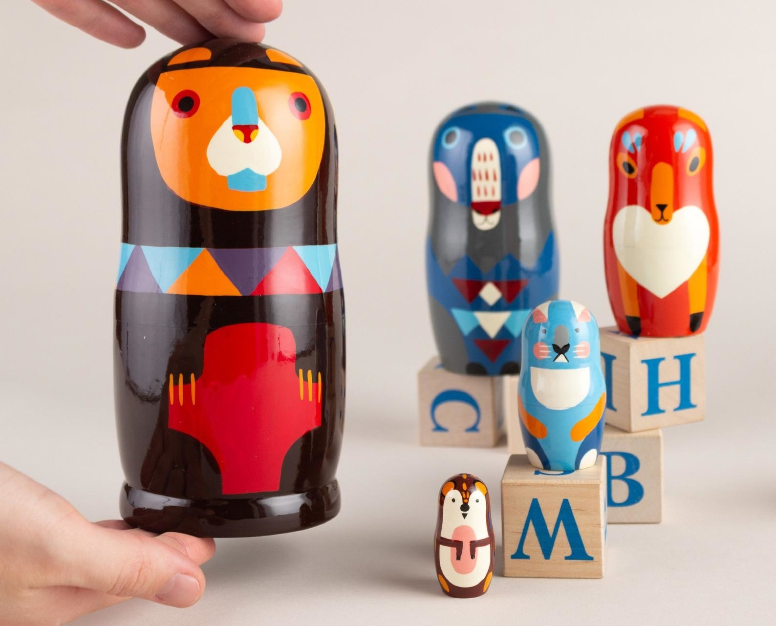 Five colorful Russian nesting dolls of various animals
