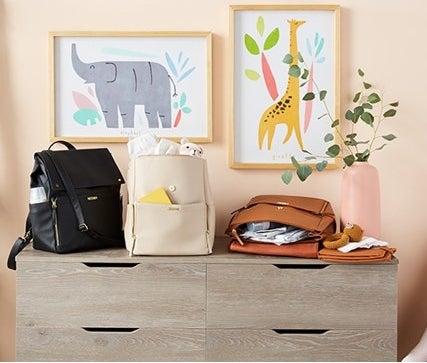 three diaper bag backpacks in a nursey room