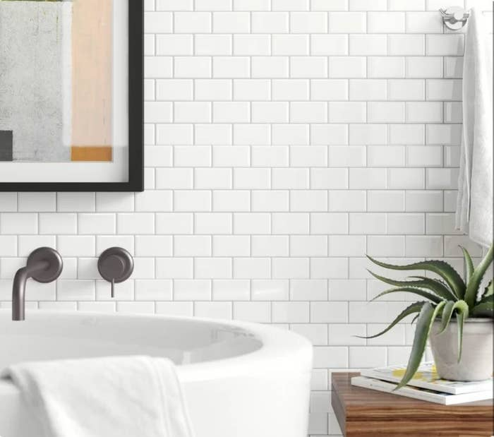 White subway tile on wall behind white bathtub