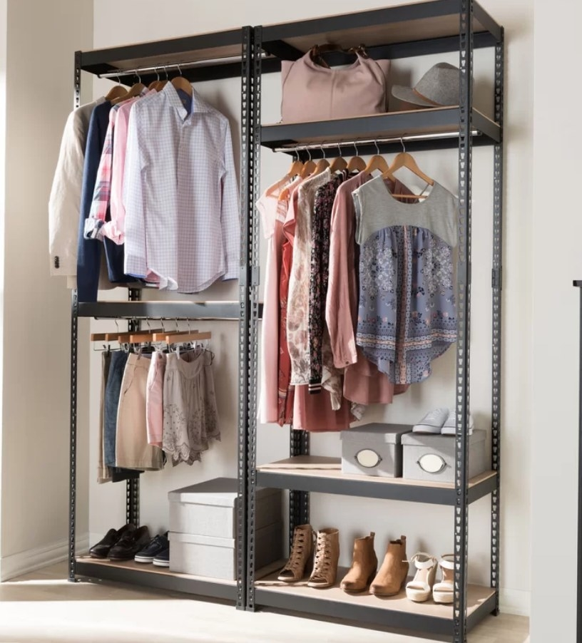 Black metal organization system with two hanging racks on left side, hanging rack on the other side with shelf above and underneath