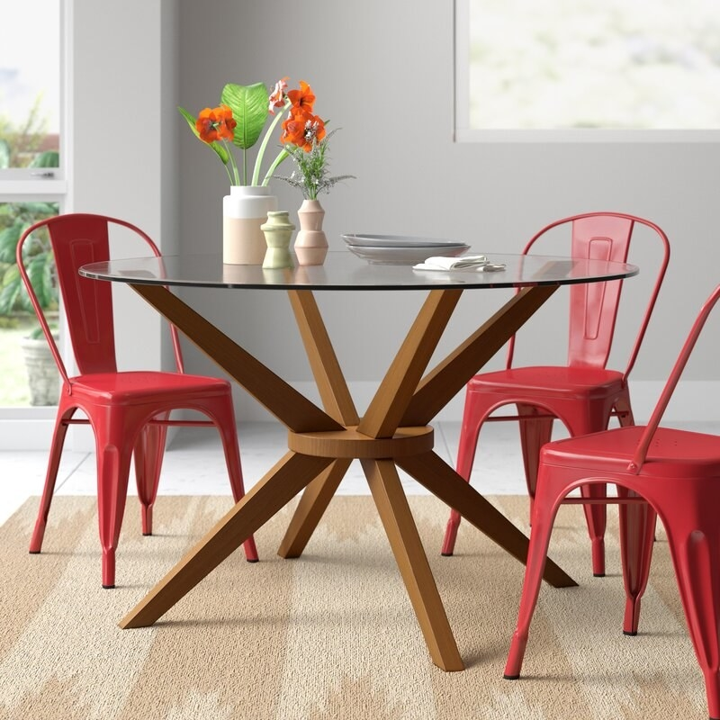 A round dining table with glass top and sculptural wooden legs