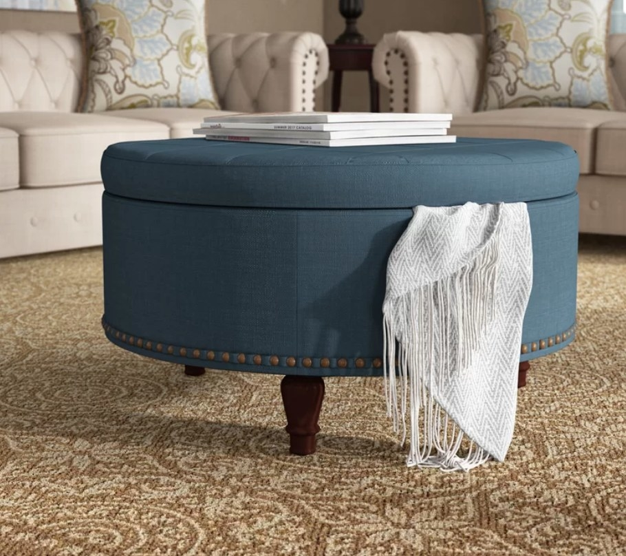 Round muted blue ottoman with white magazines on top, and white throw flowing out of storage