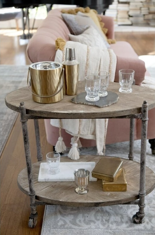 Gold stainless steel cocktail set displayed with clear glasses on a wooden bar cart