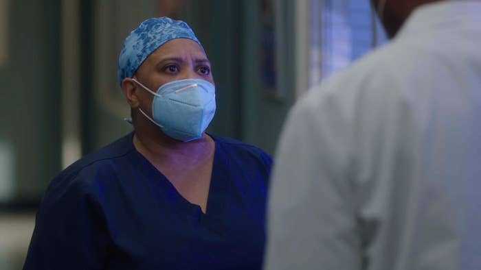 Dr. Bailey talking to someone in the hospital while wearing a surgical mask