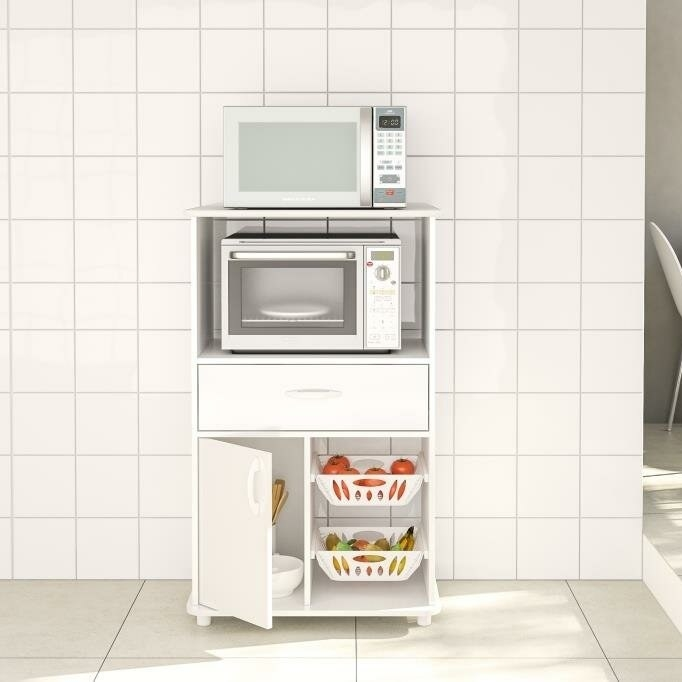 White pantry with a variety of fruit in the baskets, a microwave on top and a toaster oven inside