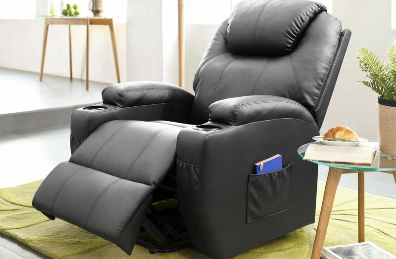 Black faux leather massage chair with blue book in its pocket