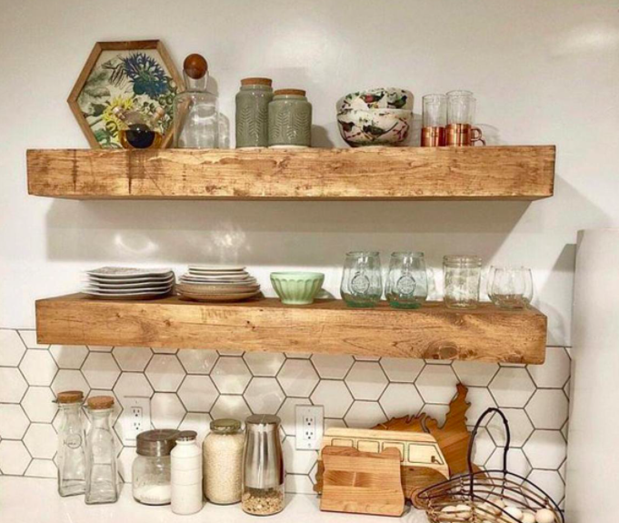 Two wooden shelves hung on a kitchen wall and stacked with plates and glasses