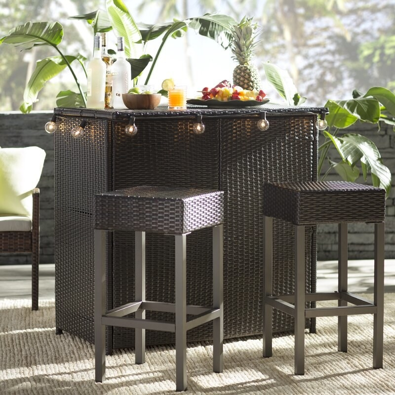 Dark brown wicker resin bar set with barstools that have gray legs