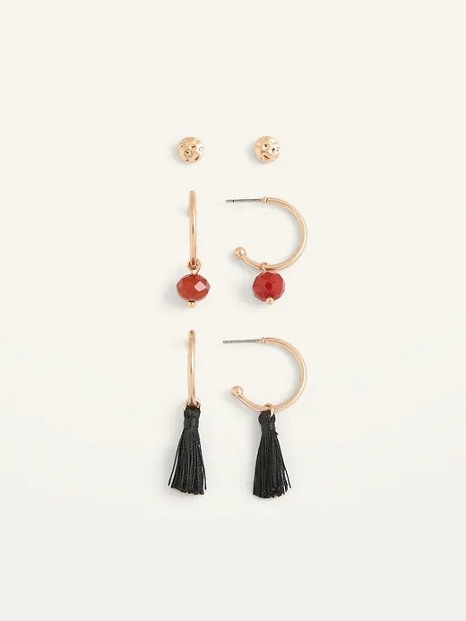 A pair of gold stud earrings displayed above a pair of red stone earrings and a pair of black tassel earrings