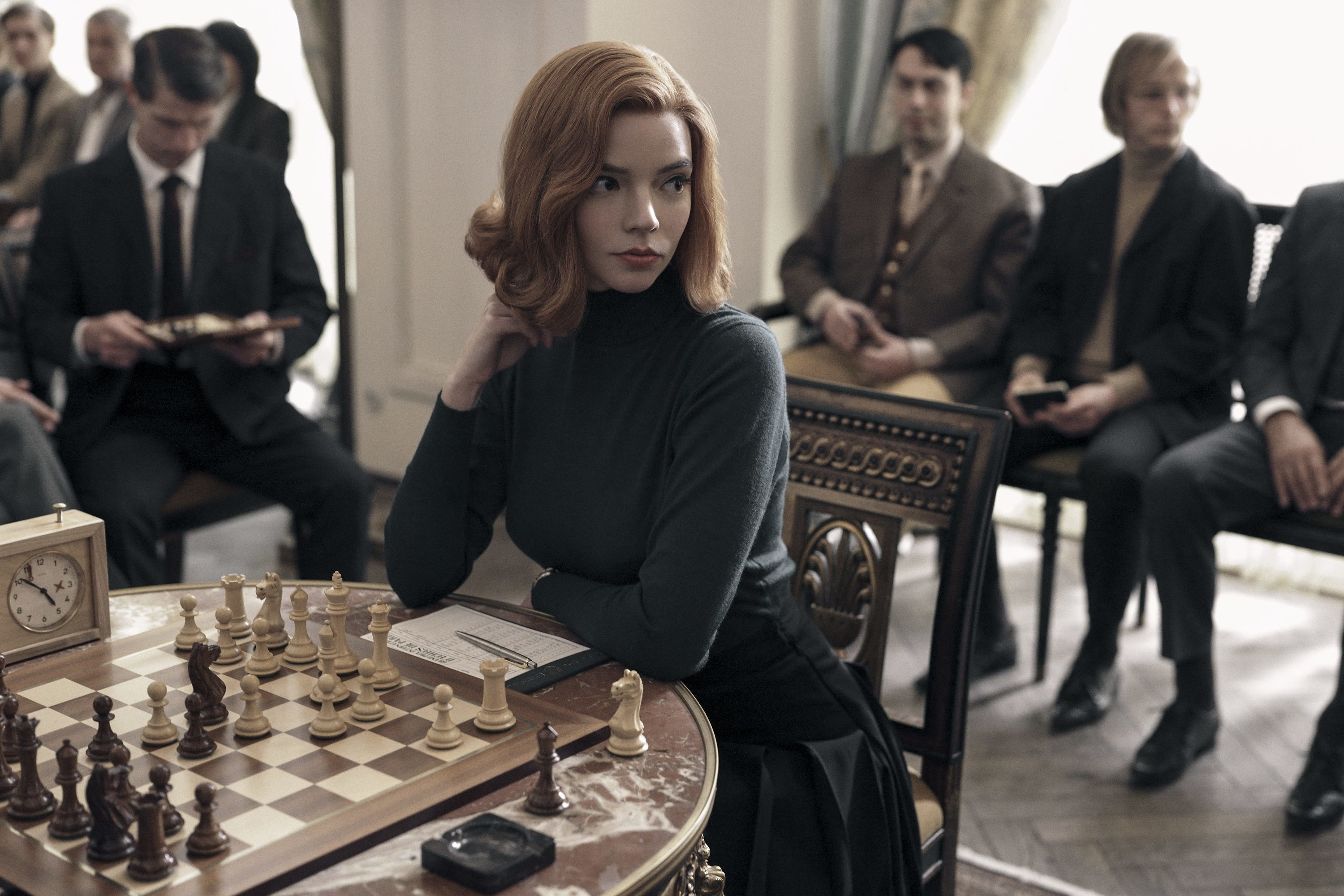 Anya Taylor-Joy as Beth Harmon in The Queen's Gambit sitting during a chess match