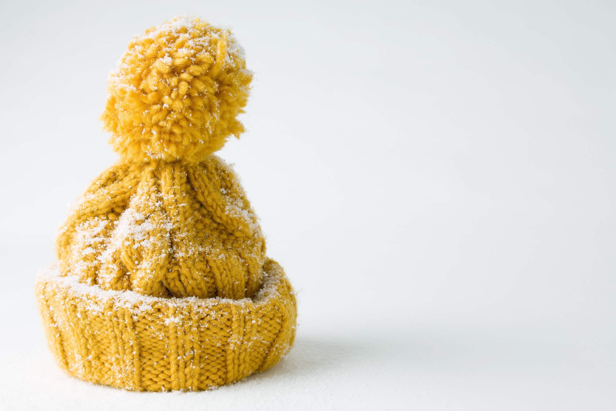 Knit yellow hat covered in snow.