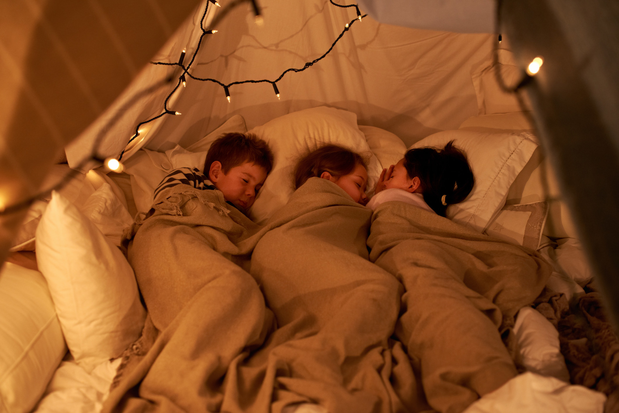 Children asleep surrounded by pillows and blankets in fort with string lights.