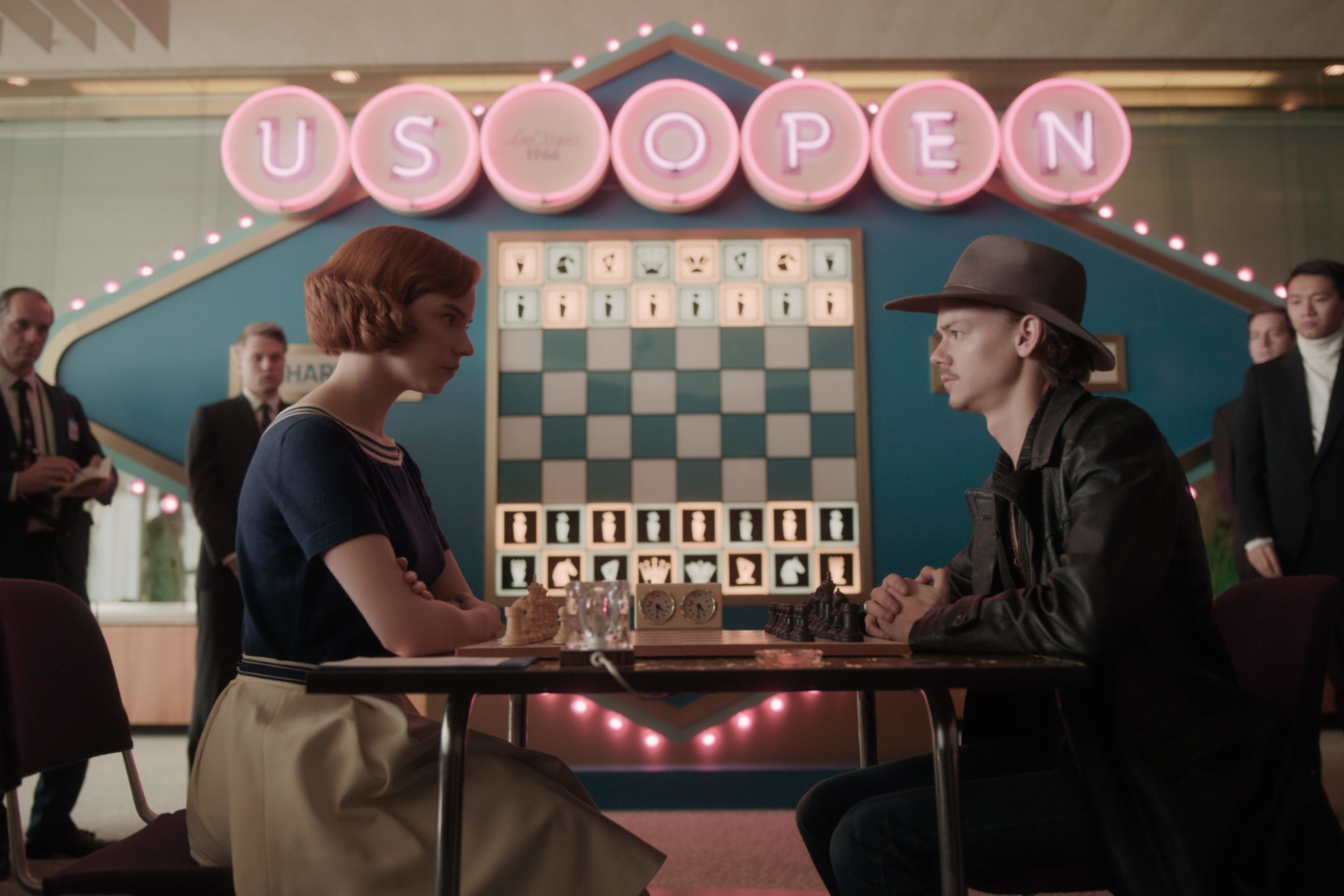 Beth and Benny face off in a chess match as several people watch