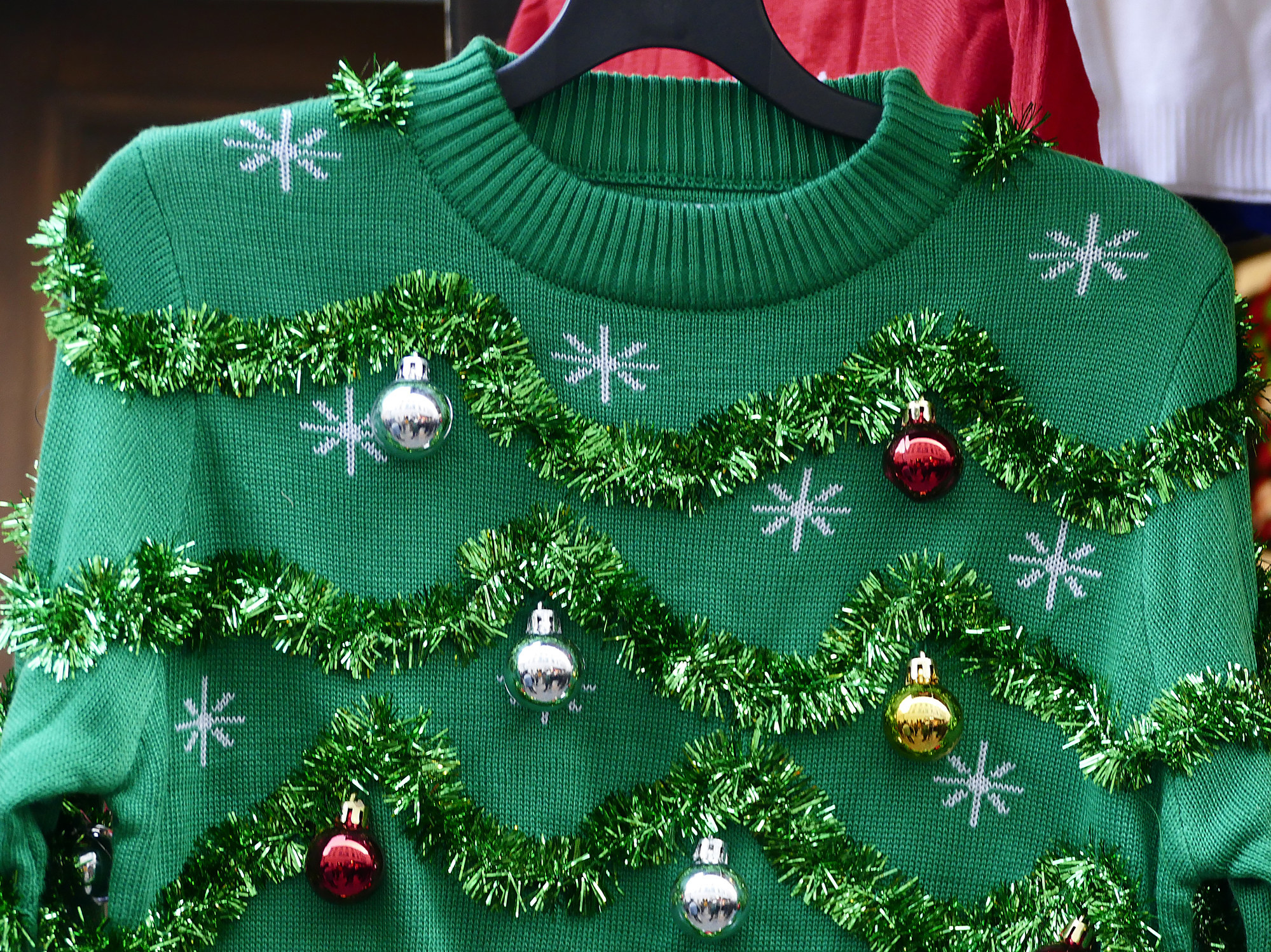 Green ugly holiday sweater covered in small ornaments.