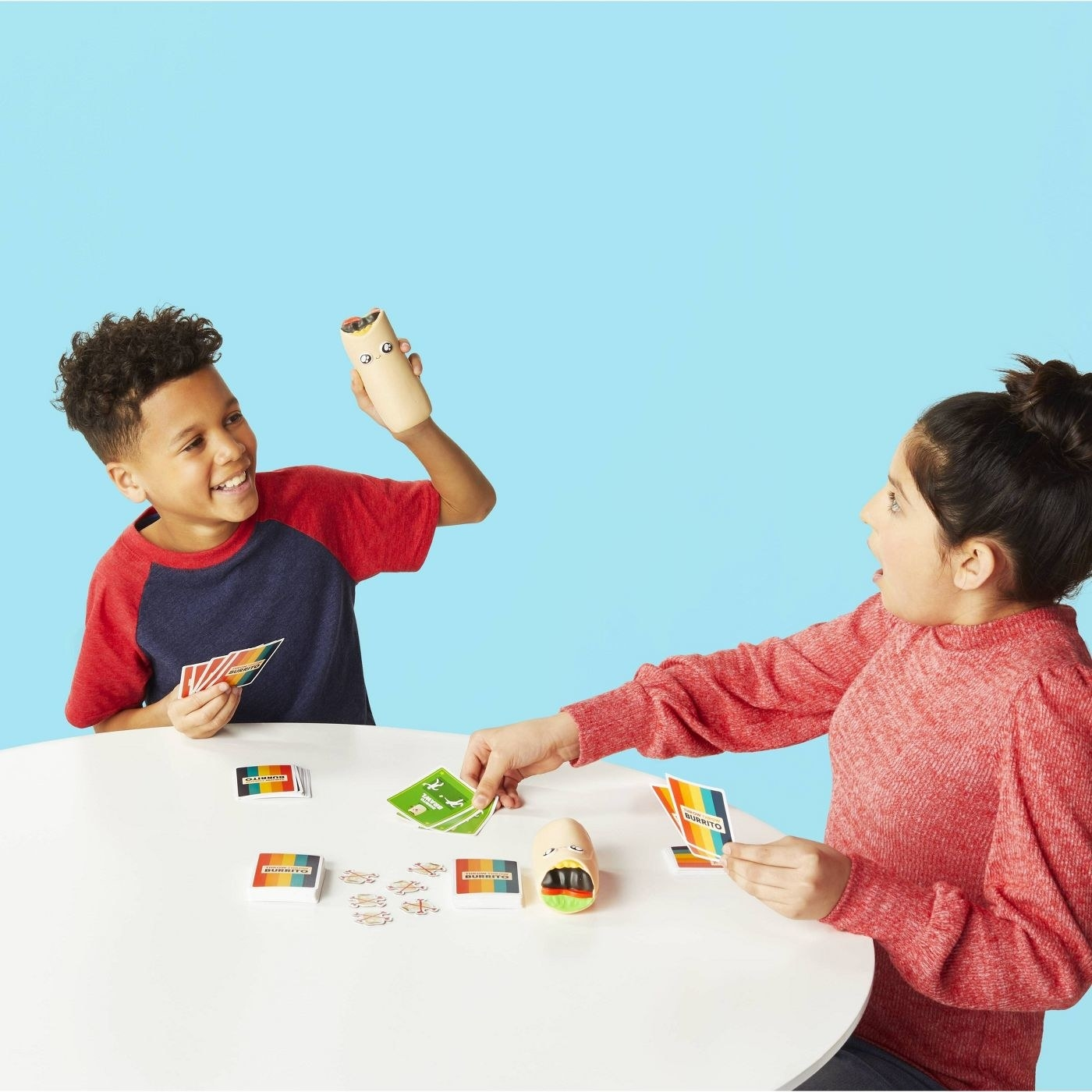 Children throwing a burrito plush toy while using the deck of cards