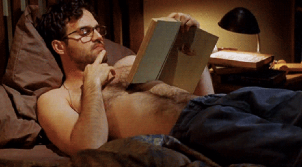 Mark Ruffalo reading a book in bed while shirtless