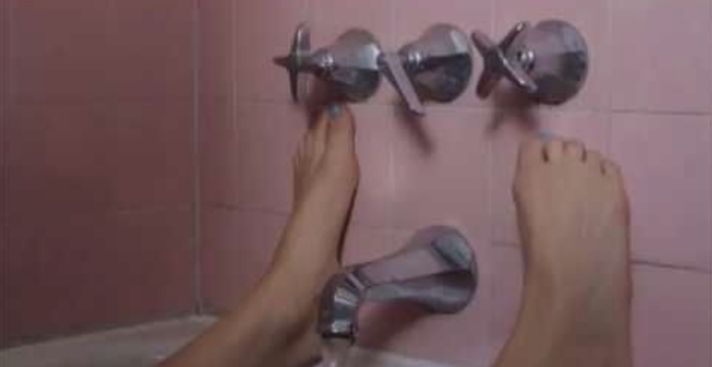 """A close-up of a Saoirse Ronan's character in the bath with her feet against the wall and the faucet running near her private parts in """"Lady Bird"""""""