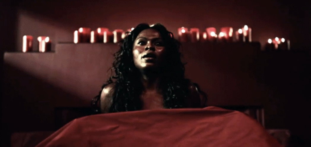 """A woman lying in bed with red sheets covering her in """"American Gods"""""""