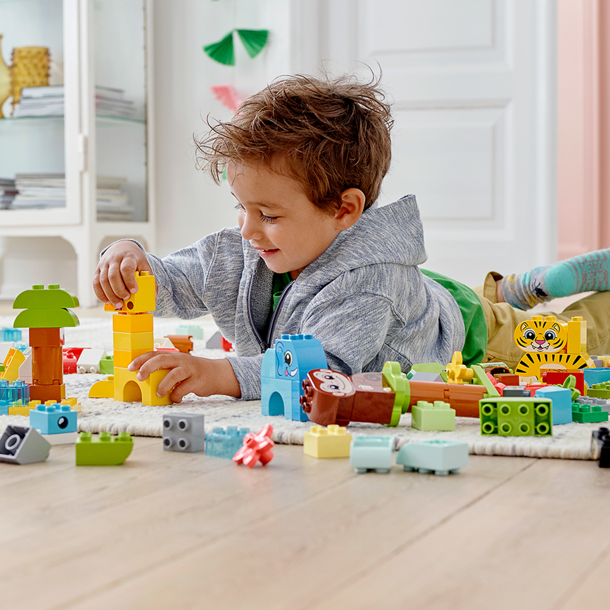 A child playing with the brightly colored LEGO blocks