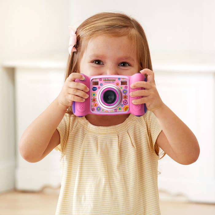 child holding the pink Vtech Kidizoom camera with floral design